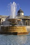 Fountain in Trafalgar square with national portrait gallery in the background. With blue sky stock photography