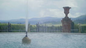 Fountain in Tuscany. Medium wide handheld high dynamic range shallow depth of field slow motion shot of a fountain in a dramatic Tuscany scene, including a stock video footage