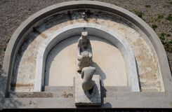 Fountain with two stone human sculpture in Trieste in Friuli Venezia Giulia (Italy). Photo overhead shot of a fountain that is located in a garden next to the Royalty Free Stock Image