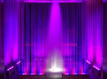 Fountain, violet illuminated flowing water by night abstract as background Stock Photo