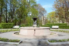 Fountain water feature in Tower`s Square in Tallinn, Estonia. Surrounded by diverse trees in spring stock photography