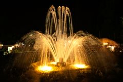 Fountain water splashing on water surface of park at night. Colorful light of Fountain water splashing on water surface of park at night stock image
