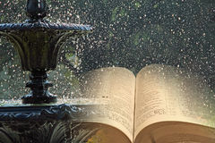 Fountain of waters of life. Concept photo of open bible with fountain water running through pages denoting the parables of christ jesus fountain of waters of stock photography