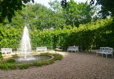 Fountain and white garden benchs in quiet green park Stock Image
