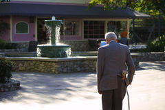 Fountain of youth. Water fountain with young boy playing and old man walking up to it Royalty Free Stock Image