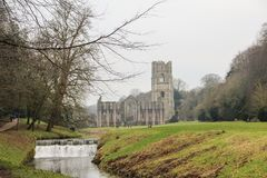 Fountains Abbey with a waterfall. Ruins of Fountains Abbey with a waterfall, Yorkshire, England, UK Stock Images
