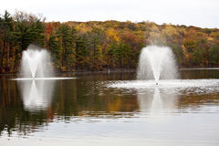 Fountains. Autumn forest lake with a fountains and a reflection Royalty Free Stock Photo