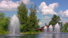 Fountains in city park. Nature landscape with green trees, lake, fountains stock footage