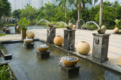 Fountains and garden ornaments. Terraced area of hotel garden Sanya, Hainan island, China, showing fountains cascading water into rectangular pool with garden Stock Photography
