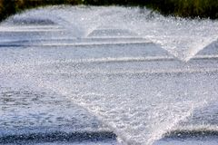 3 Fountains in a pond therefore water treatment process. High speed shutter royalty free stock photo