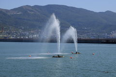 Fountains in the sea. Spray fountains in the bay. Sea port Stock Image