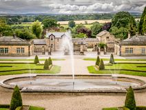 Fountains in a botanical garden, fields and clouds in the background royalty free stock image