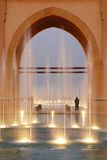 Fountains and stone arch. Illuminated fountains under stone arch with person standing in background, Kuwait Stock Photo