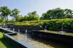 Fountains in verdant green of sunny summer afternoon Stock Photography