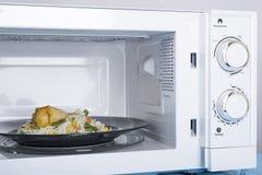 Four à micro-ondes blanc, sur une surface en bois bleue pour la nourriture de chauffage Photo stock