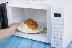 Four à micro-ondes blanc, sur une surface en bois bleue pour la nourriture de chauffage Image libre de droits