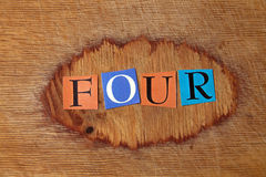 Four. Text on a wooden board royalty free stock photo
