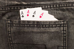 Four ace cards inside gray jeans back pocket Stock Images
