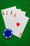 Four Aces. And a blue poker chip stock photography