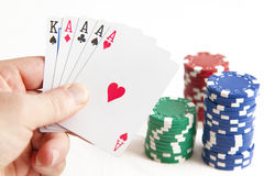 Four Aces. A poker player holds a hand of four aces and a king. Photographed on white and featuring stacked poker chips stock photo