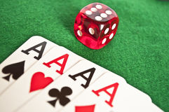 Four Aces And Red Dice On Green Background Stock Photo