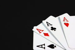 Four Aces on Black. Four playing cards, all aces, fanned out in the corner of a black background Stock Images