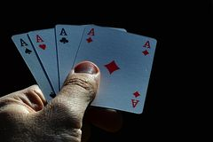 Four aces from canasta joker from French deck held in male left hand on dark background. In morning sun Royalty Free Stock Photos