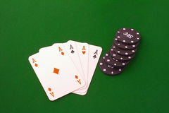 Four aces and chips. Four aces near some black chips over green carpet Royalty Free Stock Photo