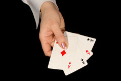 Four aces in female hand on black. Four aces in female hand isolated on black Stock Photo