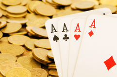 Four aces and gold coins Stock Photography