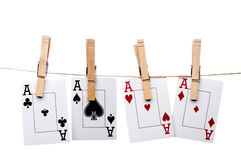 Four aces hanging from clothes pegs on a clothes l. Ine on a white background Stock Photos
