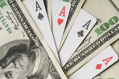 Four aces poker playing cards among U.S. dollars Royalty Free Stock Photo