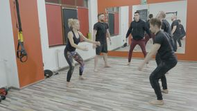 Four active young boys and a girl working out their body in a cross fit gym class by doing squats series - stock footage