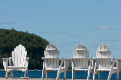 Four Adirondack Chairs by the Lake Stock Image