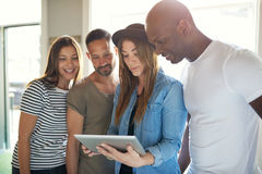 Four adults interested with something on tablet. Diverse group of four young attractive adults dressed casually while looking at something interesting on a royalty free stock photography