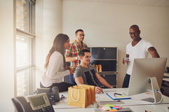 Four adults sitting around desk at work Stock Photography