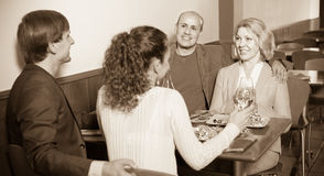 Four  adults with wine and dinner laughing in restaurant Stock Photo