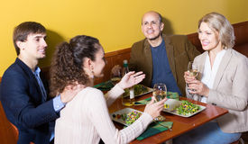 Four  adults with wine and dinner laughing in restaurant Stock Image