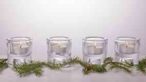 Four Advent candles in glass candlesticks on a white background, Christmas spruce branches. The imminent background of Royalty Free Stock Image