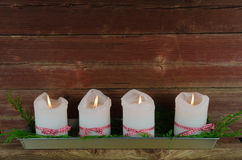 Four advent candles at an old weathered red wall Royalty Free Stock Photography