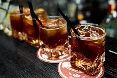 Four alcoholic cocktails whiskey with cola and lemon in glasses royalty free stock photography