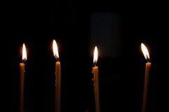Four alight candles. Over the black background Stock Photos