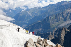 Four alpinists ascend on snow patch Royalty Free Stock Photos