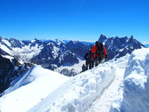 Four alpinists and mountaineer climber on Aiguille du Midi. CHAMONIX MONT BLANC french ALPS, top alpine mountains range landscape, FRANCE with clear blue sky Royalty Free Stock Image