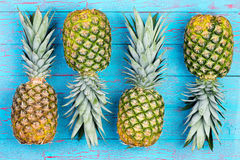 Four alternating pineapples on market table Royalty Free Stock Images