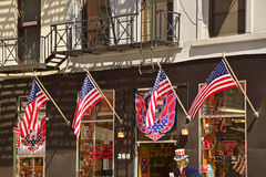 Four American flags waving in front of a Souvenir shop in New York City. New York City is one of most visited places by tourists from around the world royalty free stock photos