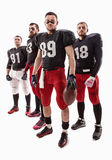 The four american football players posing with ball on white background Stock Images