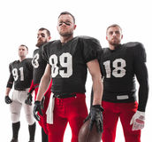 The four american football players posing with ball on white background Royalty Free Stock Photo