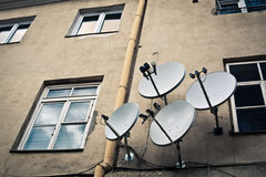 Four antennas on the beige wall. Four satellite antennas on tacky beige wall with few windows and yellow drainpipe Stock Images