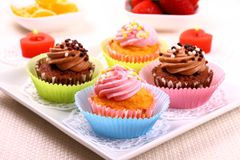 Four appetizing cupcakes on white plate Royalty Free Stock Images